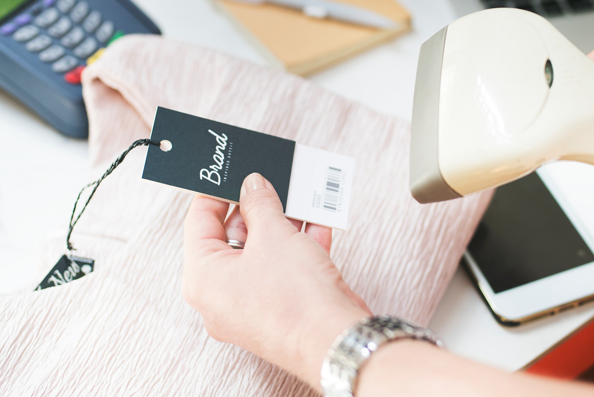 "Photo of person scanning barcode on clothing tag with the word ""Brand"""